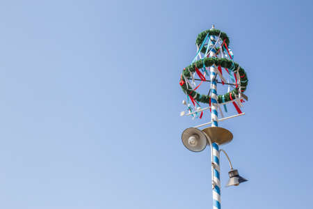 lamp on the pole: Decorated lamp pole with wreath and colored paper on a sunny day in front of blue sky