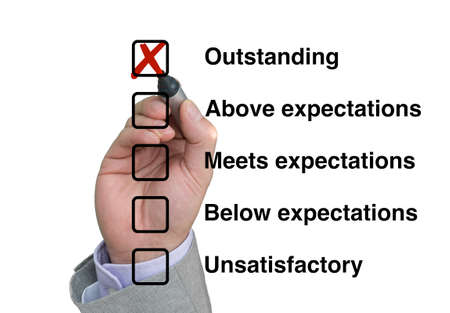 unsatisfactory: Businessman fills out performance rating checklist setting a tick mark at outstanding