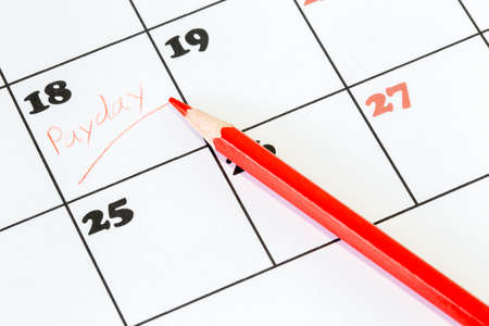 payday: Red pencil on a calendar with the word Payday written on one of the days