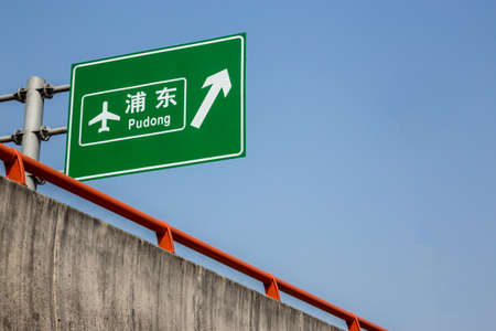 pu dong: Shanghai pudong airport directional road sign closeup with the characters for pu dong, Shanghais biggest airport