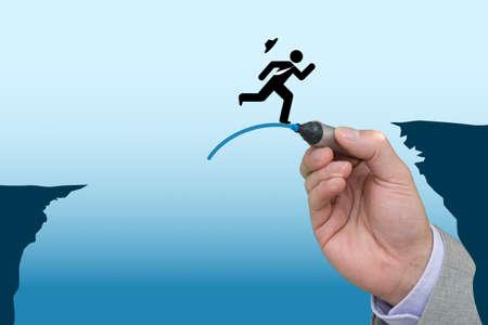 bridging the gap: Business hand draws a jump pad to help business man bridge the gap between two cliffs