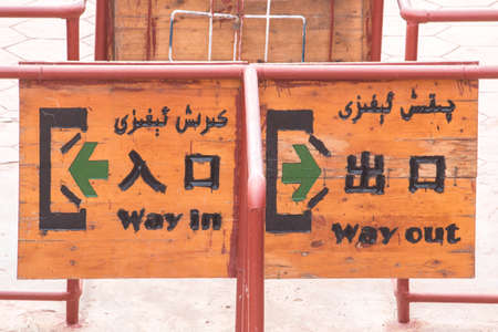 way out: Way in way out sign in chinese,english and arabic carved in wood