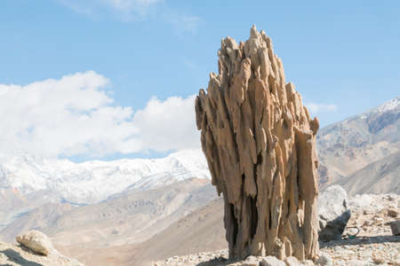 geological formation: Stalagmite like geological formation outside in front of a mountain landscape on a sunny day