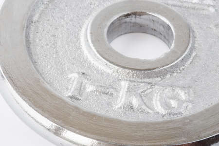 kg: Metal round weight of one kg closeup in silver