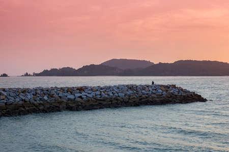 langkawi island: Silhouette watching sunset on Langkawi island in Malaysia with a reddish orange sky Stock Photo