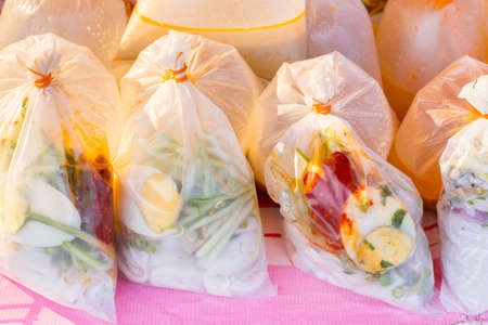 take away: Malaysian style take away noodle dish in transparent plastic bag on a local market