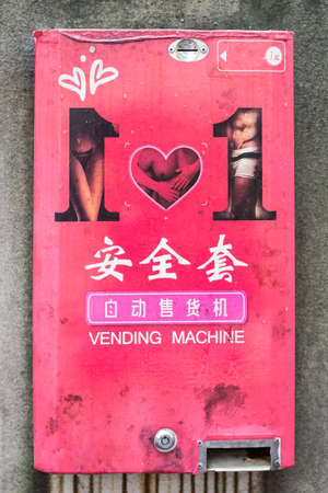 condones: Máquina expendedora de preservativos oxidada vieja en China con los caracteres chinos para la máquina expendedora de preservativos y una moneda de un RMB Foto de archivo