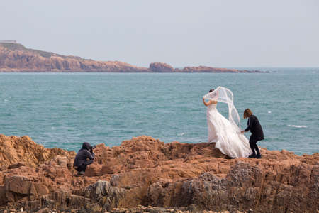 wedding photography: Wedding photography at the coast of Qingdao with a bride being prepared and photographed Editorial