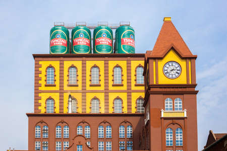 Qingdao,China 20/04/2016 Main building of the Qingdao brewery with four cans of beer on the rooftop and a clock tower