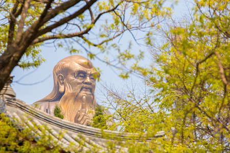 creator: A huge 36m statue of the spiritual creator of Daoism Laozi seen through a forest above a Chinese roof