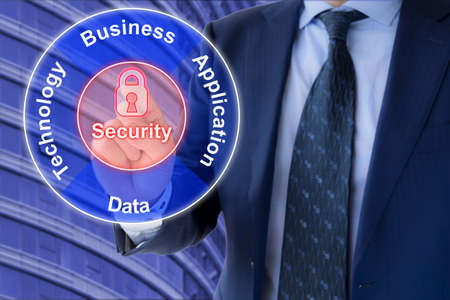 domains: The four Enterprise Architecture domains Business,Technology,Data and Application presented by a businessman in a suit in front of an office building clicking on a security padlock in the middle Stock Photo