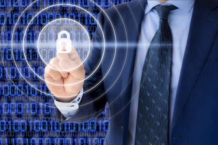 Businessman in a blue suit presses a glowing padlock in front of a digital background internet cybersecurity concept