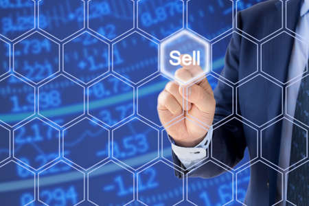 ticker: Businessman in a blue suit pressing the sell button an a hexagon grid in front of a stock ticker wall
