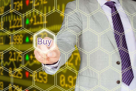 stock ticker: Businessman in a grey suit pressing the buy button an a hexagon grid in front of a stock ticker wall