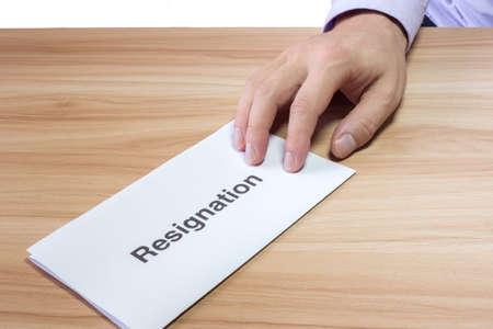 La mano de un hombre de negocios entregue una carta de renuncia en una mesa de madera