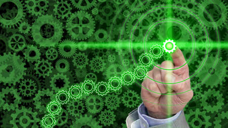 sized: Different sized an shaped green cogs and gears background with a hand pressing a glowing green gear in a chain