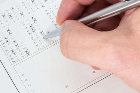 ballpen: Hand with a ballpen filling out an exam answer sheet