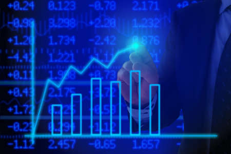 stock ticker: Businessman pressing a glowing chart in front of a stock ticker wall background