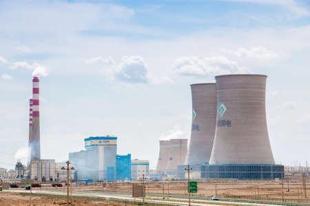 xinjiang: Xinjiang,China 09032015 Chinese nuclear power plant with surrounding buildings in front of a blue cloudy sky in Xinjiang China �ditoriale