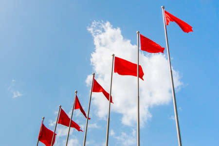 signle: Row of seven red flags in front of a blue sky on a sunny day with a signle white cloud