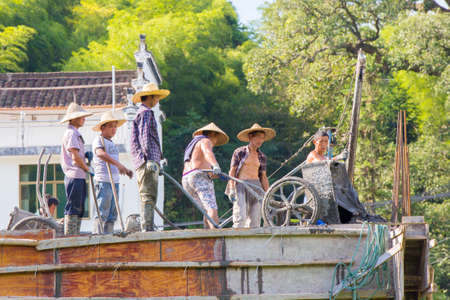 Likeng,China - Construction workers with straw hats working on a roof with traditional tools emptying a cart with concrete Editorial