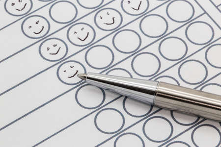 smileys: Performance evaluation sheet with a silver pen and hand drawn smileys in circles