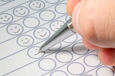 smileys: Hand filling out a performance evaluation sheet with a silver pen drawing smileys in circles