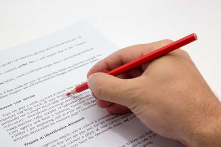 Paper with text and some wrong spelling corrected and a hand with a red pencil proofreading concept Editorial