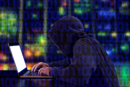 hoody: Hacker in a green hoody sitting in front of a notebook with colored server background and binary streams cybersecurity concept Stock Photo