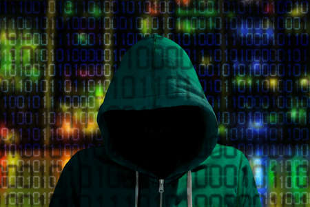Hacker in a green hoody standing in front of a colored server background with binary streams cybersecurity concept