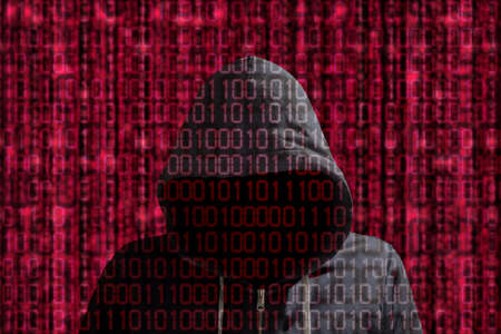 Hacker in a grey hoody standing in front of a red datastream background of binary streams cybersecurity concept