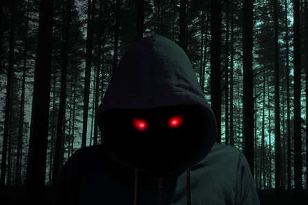 creepy alien: Creepy dark man with glowing red eyes in a black forest halloween concept