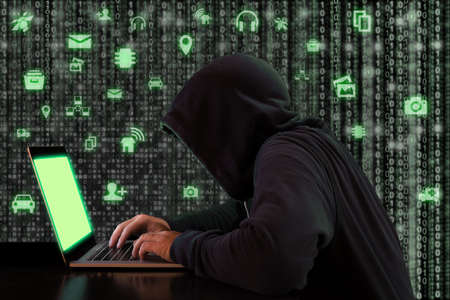 Hacker works at a notebook in front of a digital background with green internet of things icons cybersecurity concept