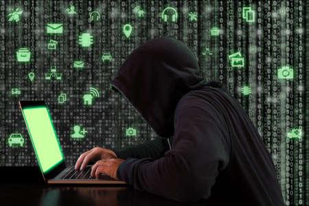 Hacker werkt op een notebook in de voorkant van een digitale achtergrond met groene internet van de dingen pictogrammen cybersecurity-concept