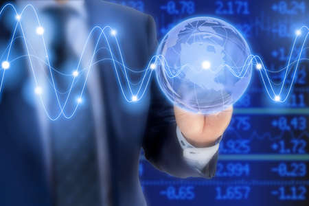 ticker: Businessman in a blue suit tapping on a glass globe in front of a stock ticker wall with glowing waves global business concept