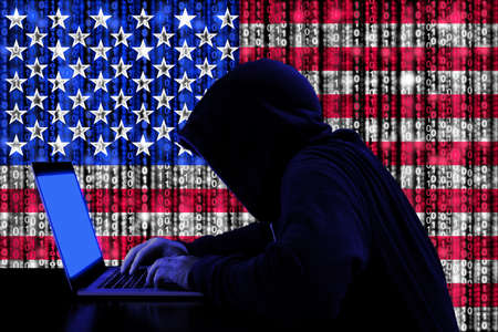 Hacker in a dark hoody sitting in front of a notebook with digital us flag and binary streams background cybersecurity concept Standard-Bild