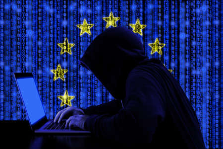 Hacker in a dark hoody sitting in front of a notebook with digital european flag and binary streams background cybersecurity concept