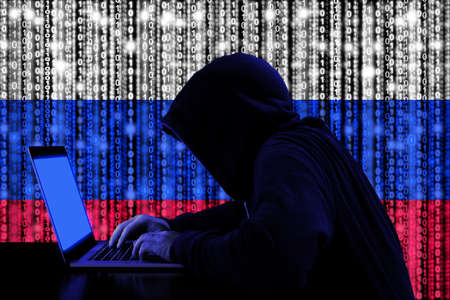Hacker in a dark hoody sitting in front of a notebook with digital russian flag and binary streams background cybersecurity concept Stockfoto