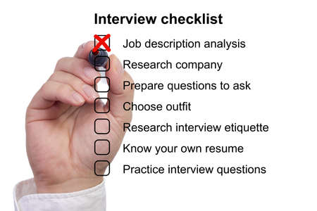 Hand crosses off the first item on a preparation checklist to prepare for job interview 版權商用圖片