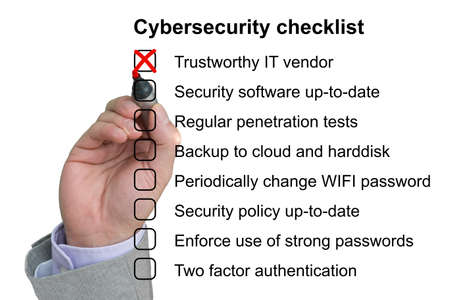 Hand crosses off the first item of a cybersecurity checklist on white background