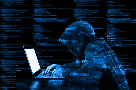 Hacker in a blue hoody standing in front of a code background with binary streams and information security terms cybersecurity concept