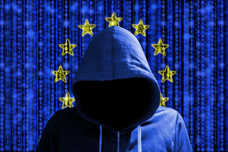 Hacker in a dark red hoody in front of a digital european flag and binary streams background cybersecurity concept