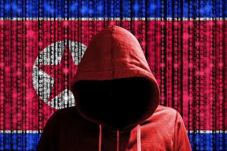 Pirata informático en una sudadera con capucha del rojo oscuro delante de una bandera coreana digital y de un concepto de ciberseguridad del fondo de las secuencias binarias Foto de archivo - 73793953