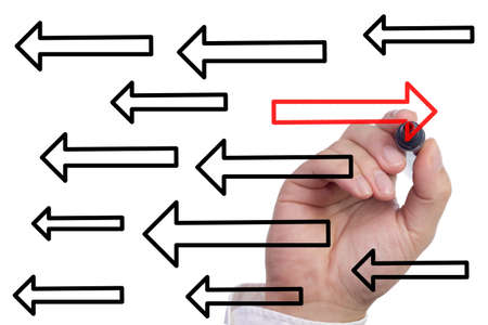 differentiation: Hand drawing a red arrow in the opposite direction of multiple black arrows Stock Photo