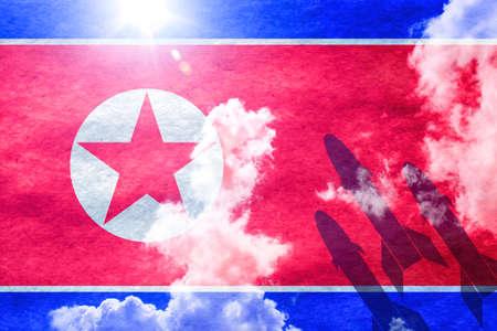 Corea del Norte bandera brillando a través de un fondo de cielo azul soleado y 3 misiles a partir de la derecha Foto de archivo