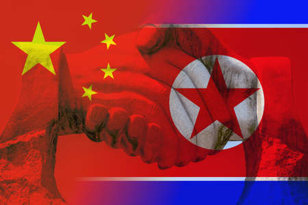 Giant stone handshake shining through the chinese and north korean flag partnership concept