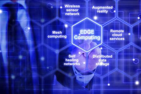 파란 옷을 입은 IT 전문가가 특정 키워드로 둘러싸인 말 가장자리 컴퓨팅으로 육각형 타일을 만집니다.