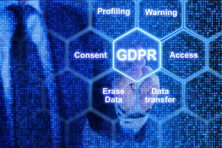 IT exppert touching a tile in a hexagon grid with GDPR keywords Stok Fotoğraf