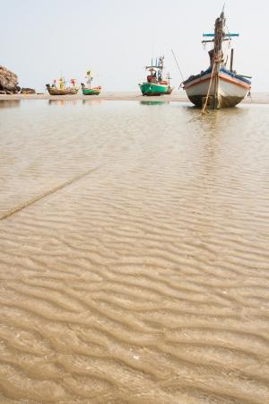 Small fishing boats on sand photo
