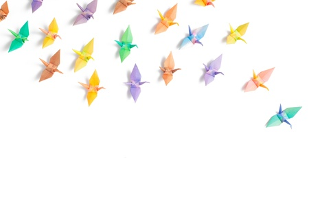 crane origami: Colorful paper birds on white background.